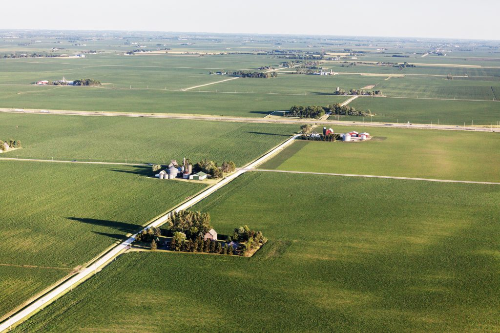 Aerial view of Farmland in Northern Illinois. Late afternoon  in June. Farms, highway, country road and crop fields. (Aerial view of Farmland in Northern Illinois. Late afternoon  in June. Farms, highway, country road and crop fields., ASCII, 117 comp